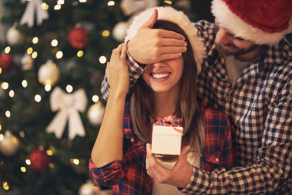 Liebespaar vor Weihnachtsbaum mit Geschenk