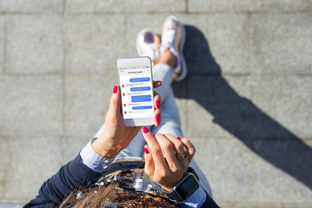 Frau nutzt Facebook Messenger am Smartphone