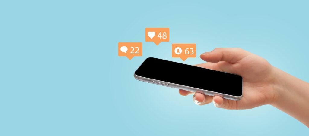 Frau haelt Smartphone mit Like und Kommentar Icons