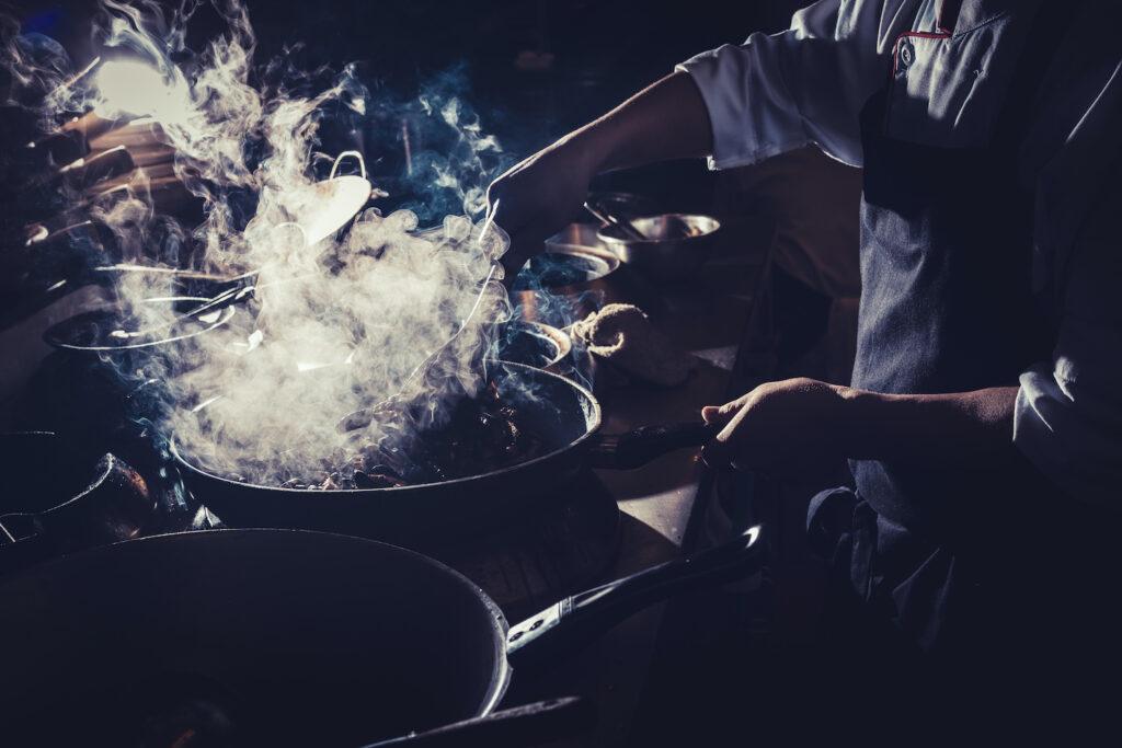 Koch der in Pfanne Essen zubereitet