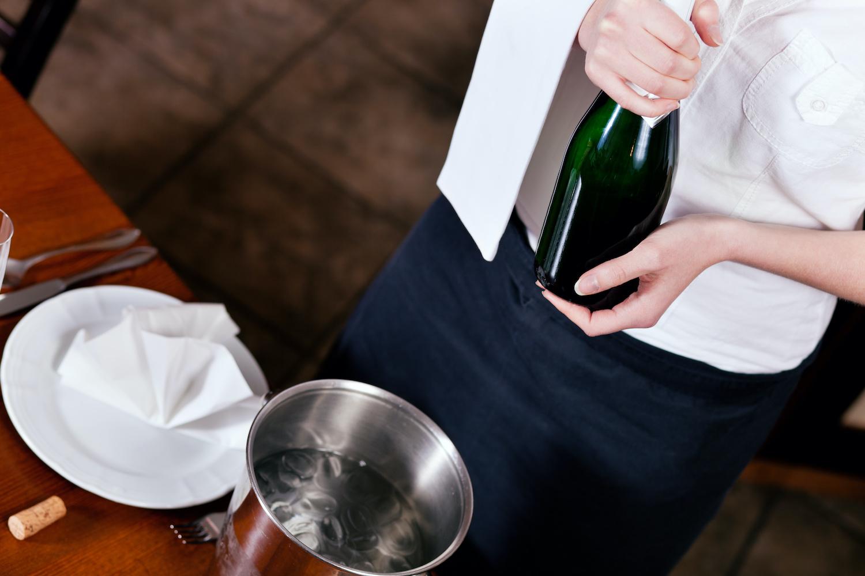 Kellnerin mit Sektflasche