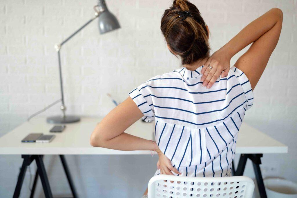 Frau im Buero mit Rueckenschmerzen