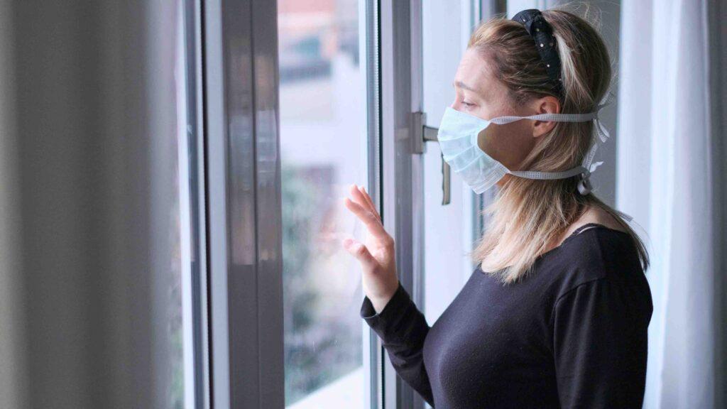 Corona-Krise: Frau mit Mundschutz zuhause