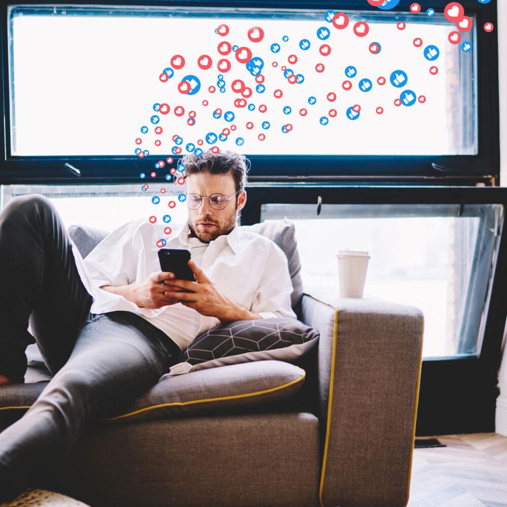 Mann auf der Couch auf Social Media Facebook und Instagram mit Handy