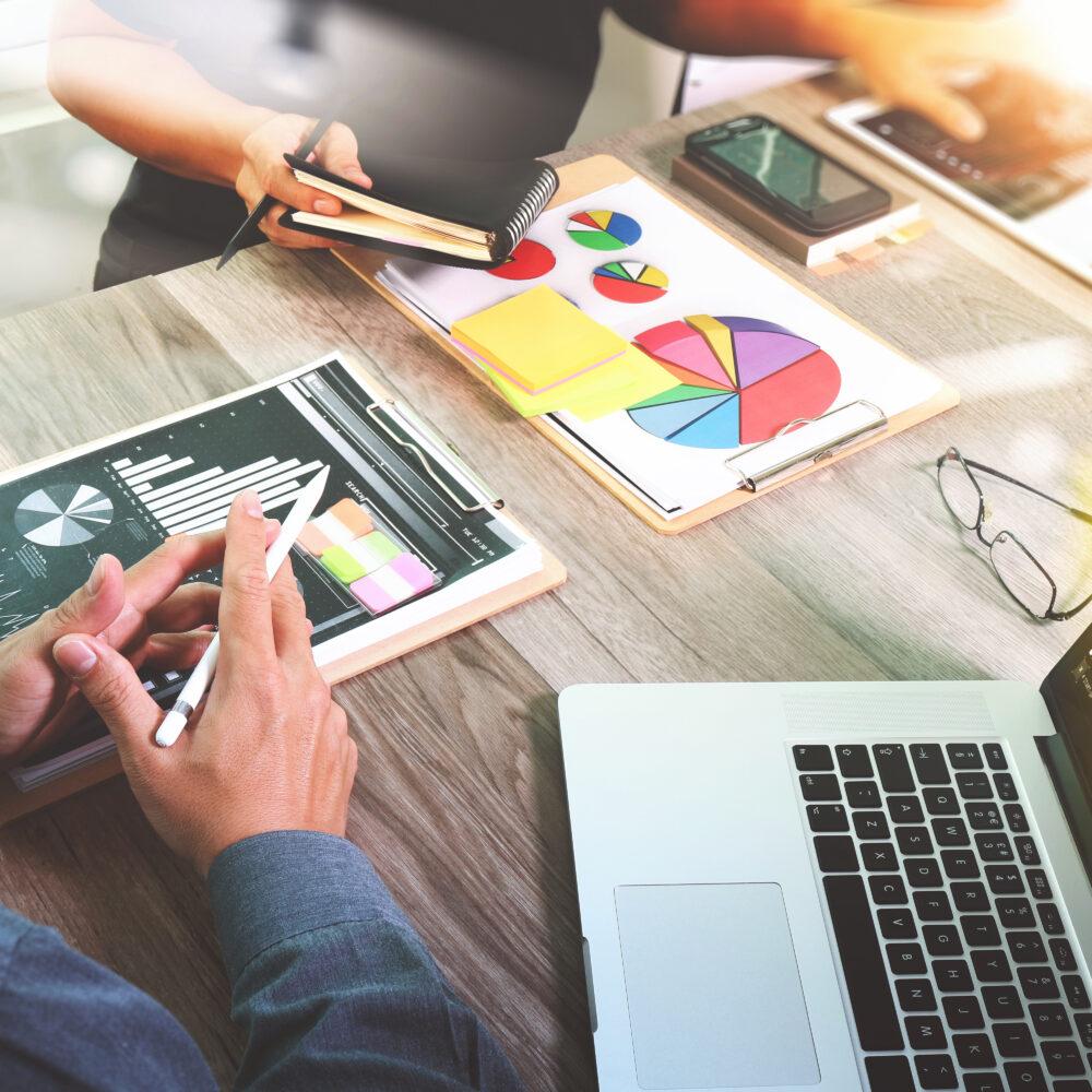Tisch mit Haenden, Laptop, Brille, Smartphone, Stifte, Plaene