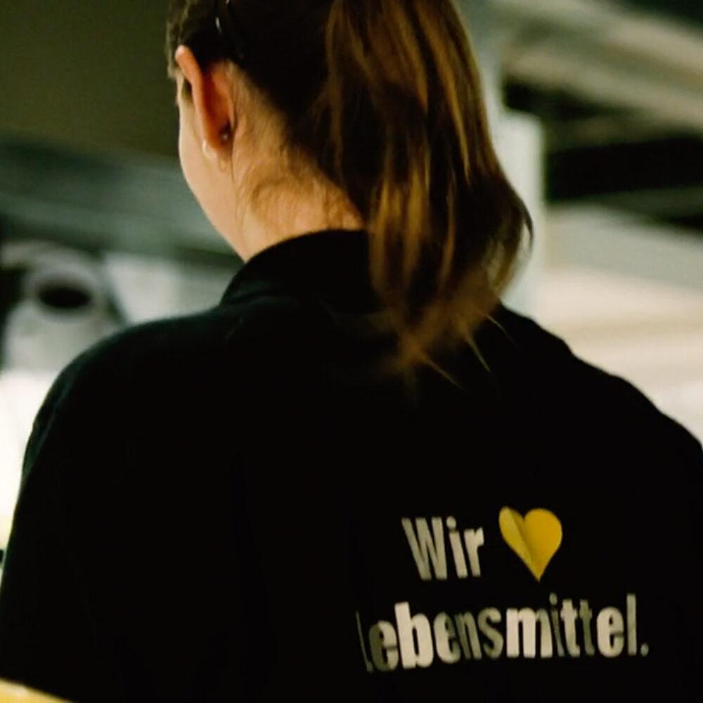 EDEKA Juniorengruppe e.V. Imagefilm EDEKAner mit T-Shirt mit Schriftzug Wir lieben Lebensmittel