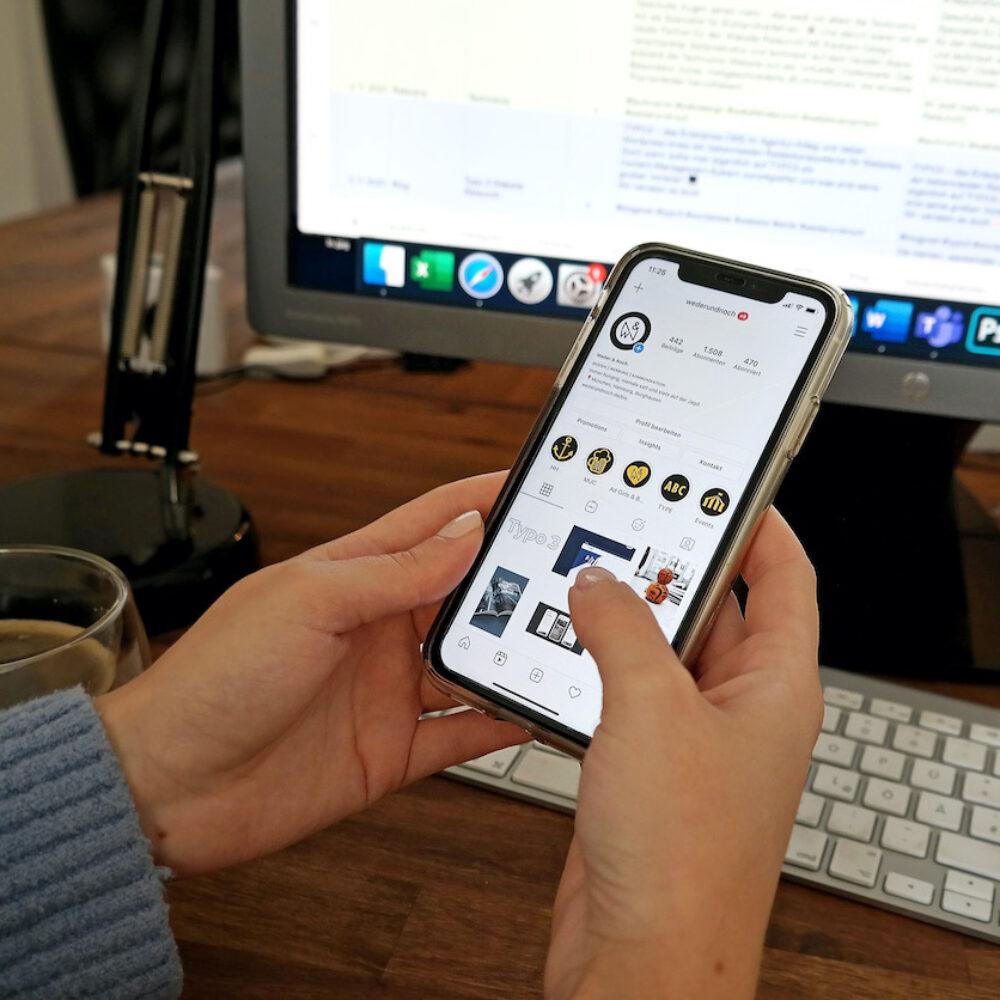 Frau mit Smartphone in der Hand vor Computer