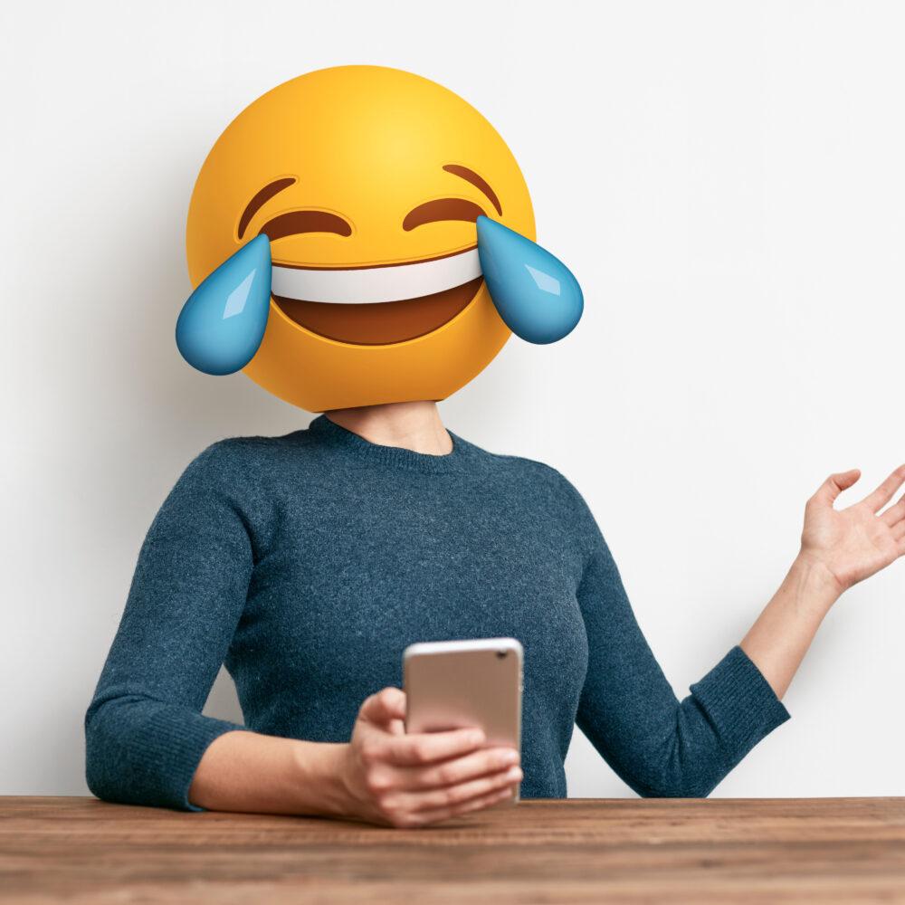 Frau mit Handy in der Hand und Lach-Emoji als Kopf