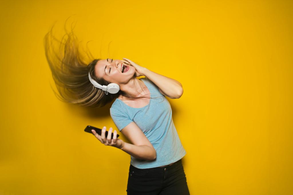 Frau mit Kopfho%CC%88rer und Fernbedienung tanzt und singt