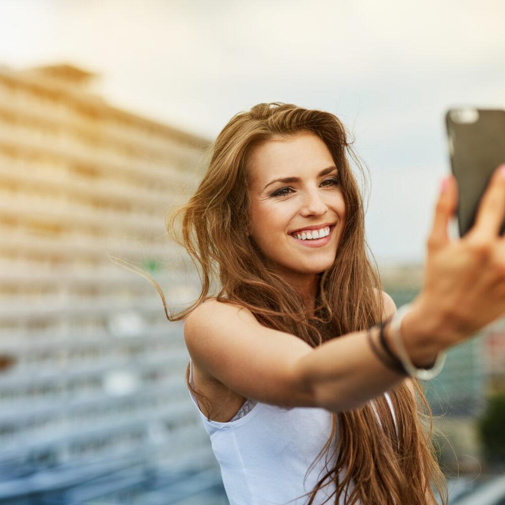 Frau mit langen braunen Haaren mit Selfie