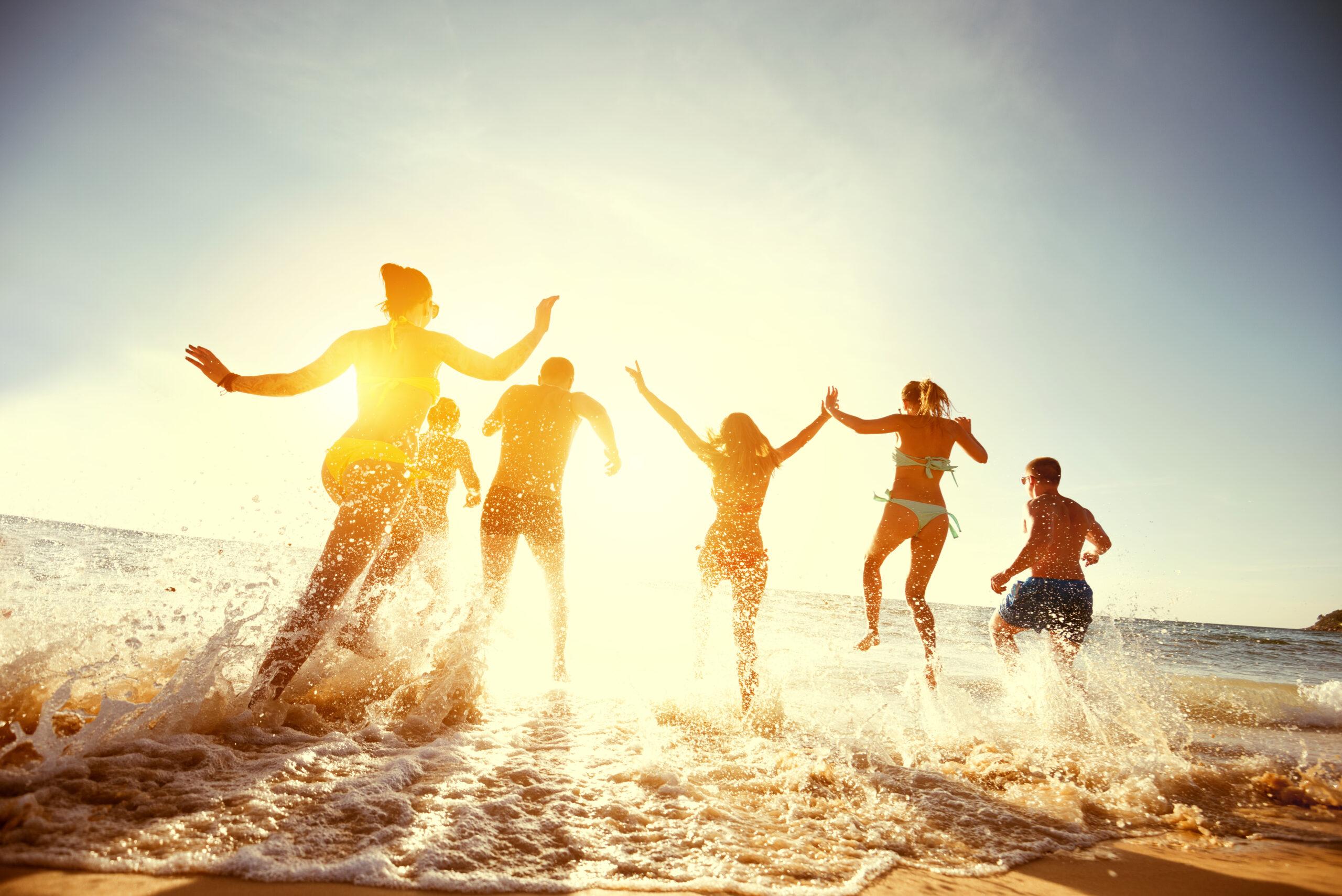 Menschen in Badeklamotten laufen ins Wasser