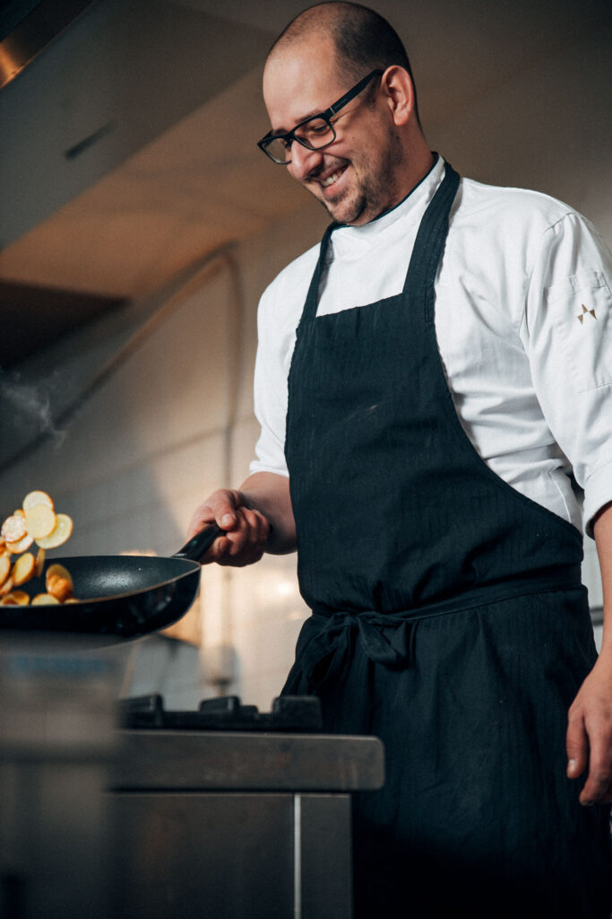Koch schwenkt Bratkartoffeln in der Pfanne
