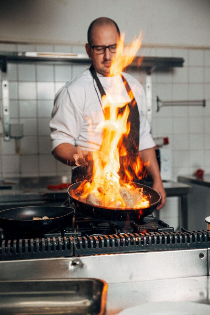 Koch hinter flammender Pfanne