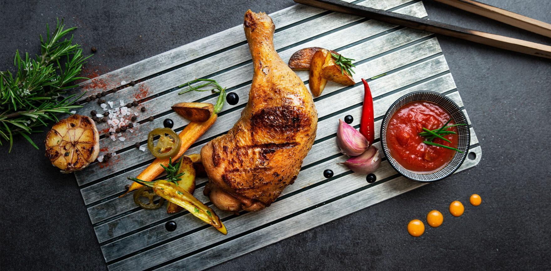 Geflügel Gross Foodfotografie Hühnchenschenkel angerichtet auf einer Aluplatte mit Chilisoße, Karotten und Kartoffeln