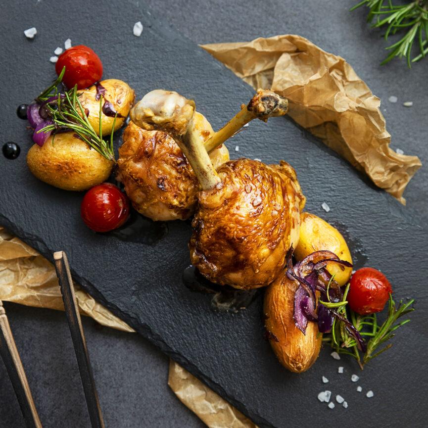 Geflügel Gross Foodfotografie Hühnchenkeulen mit Kartoffeln, roten Zwiebeln und Kartoffeln angerichtet auf einer schwarzen Schieferplatte