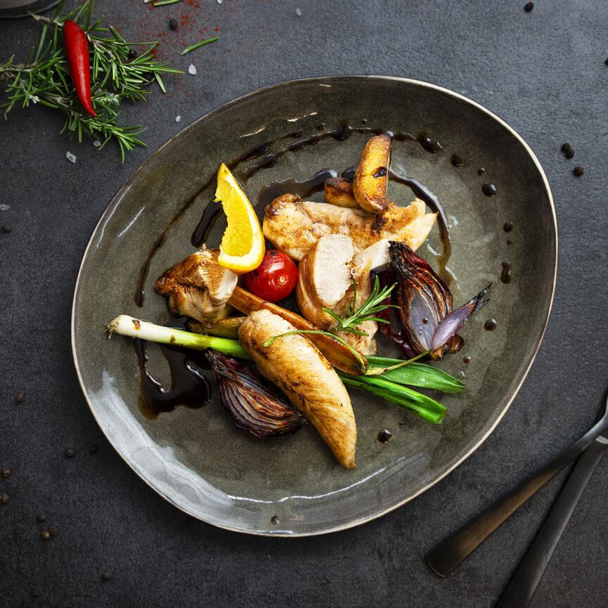 Geflügel Gross Foodfotografie Hühnchenfilet mit Lauchzwiebeln, Tomaten, Kartoffeln und roten Zwiebeln angerichtet auf einem grauen Keramikteller