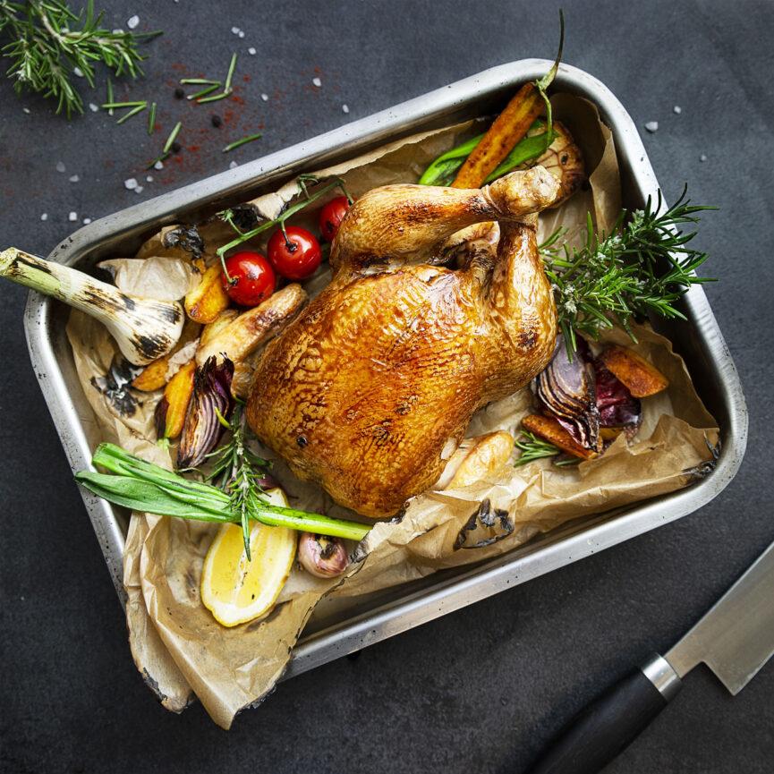 Geflügel Gross Foodfotografie Ganzes ofengegartes Huhn in einer Auflaufform mit Rosmarin, Karotten, Kartoffeln, Lauchzwiebeln und Tomaten.