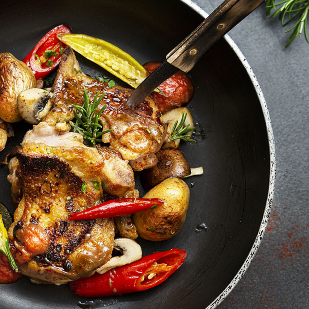 Geflügel Gross Foodfotografie Hühnchen in der Pfanne mit angebratenen Schoten, Kartoffeln und Champignons