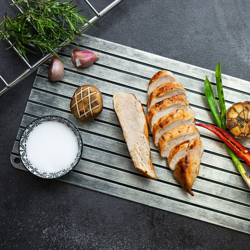 Geflügel Gross Foodfotografie Hühnchenbrust angerichtet auf einer Aluplatte mit Lauchzwiebeln, Chilischoten, Kartoffeln und gerösteten Champignon