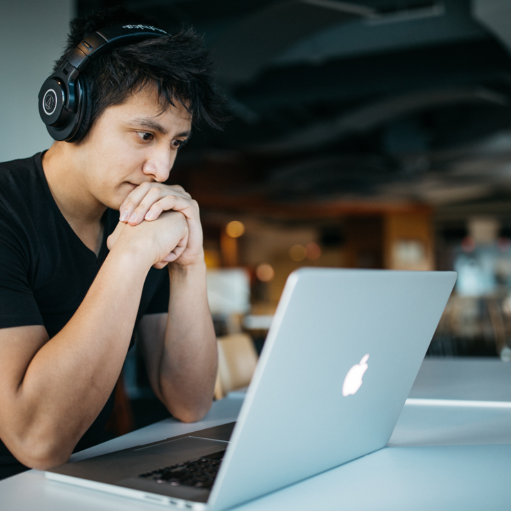 Mann mit Kopfho%CC%88rer ho%CC%88rt Musik und sitzt vor Laptop