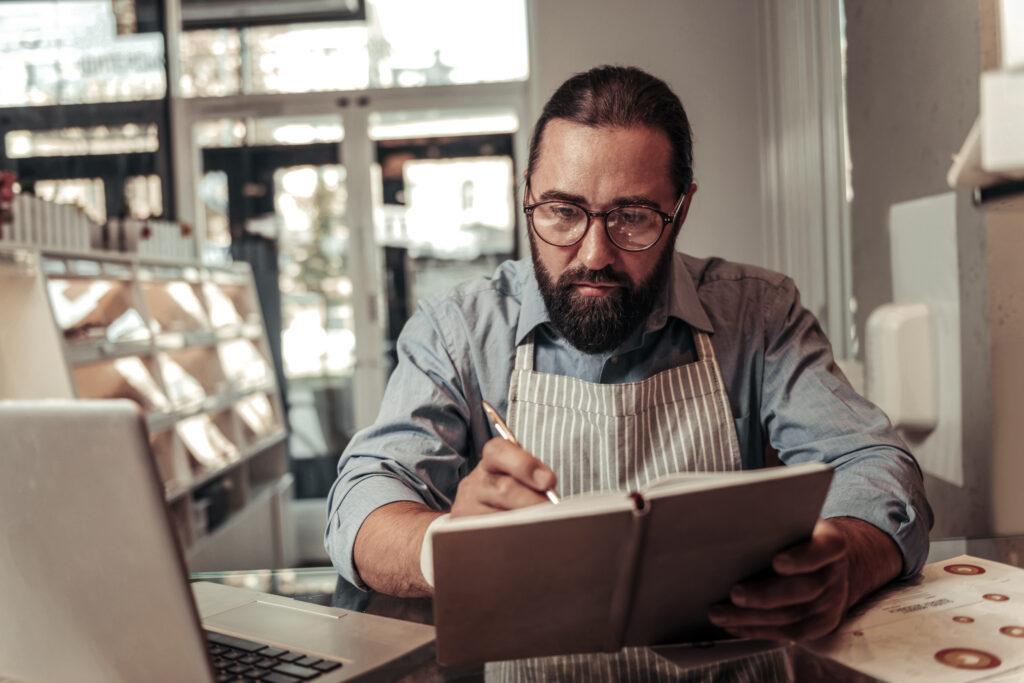 Gastronomie - Mann in Restaurant mit Notizbuch und Laptop