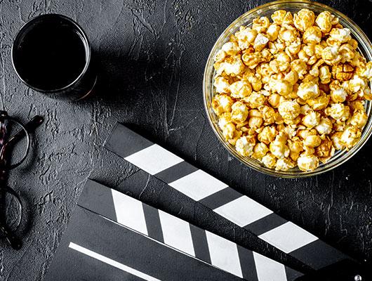 Brille, Popcorn, Becher und Regieklappe