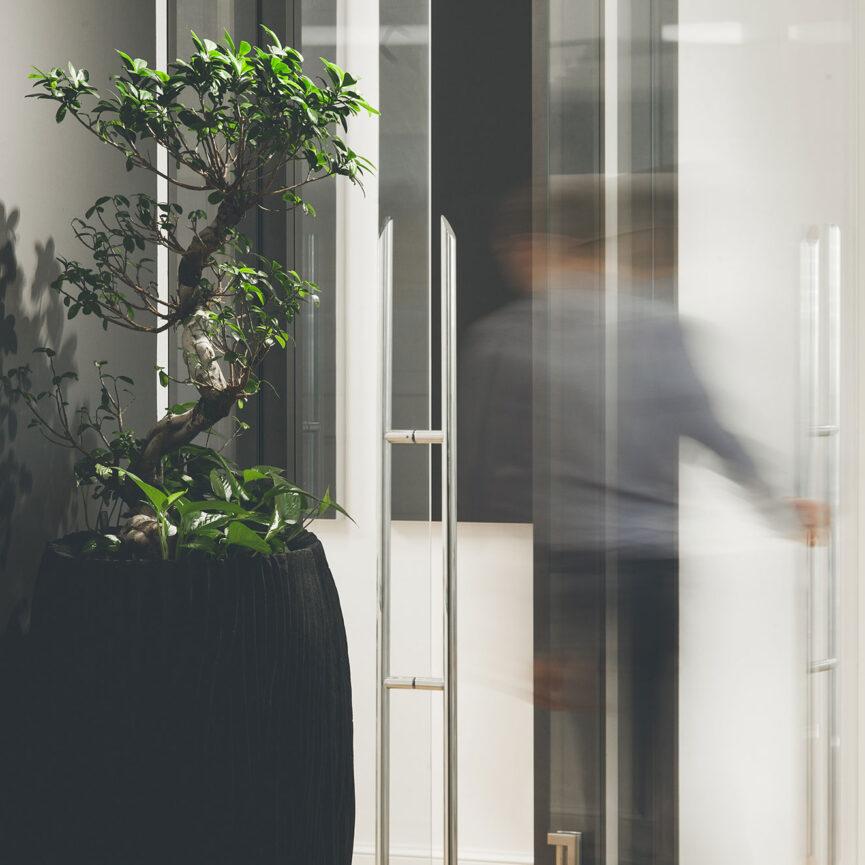 Person verlaesst Raum durch eine Glastuer